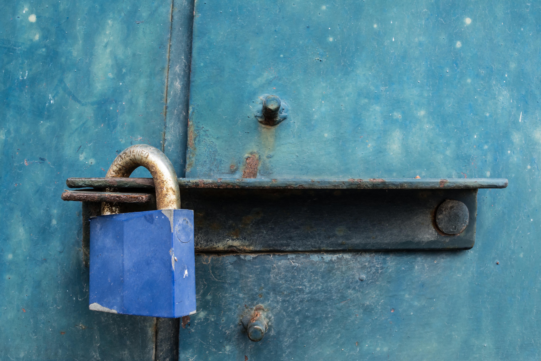 Blue padlock on rough, dirty iron door.