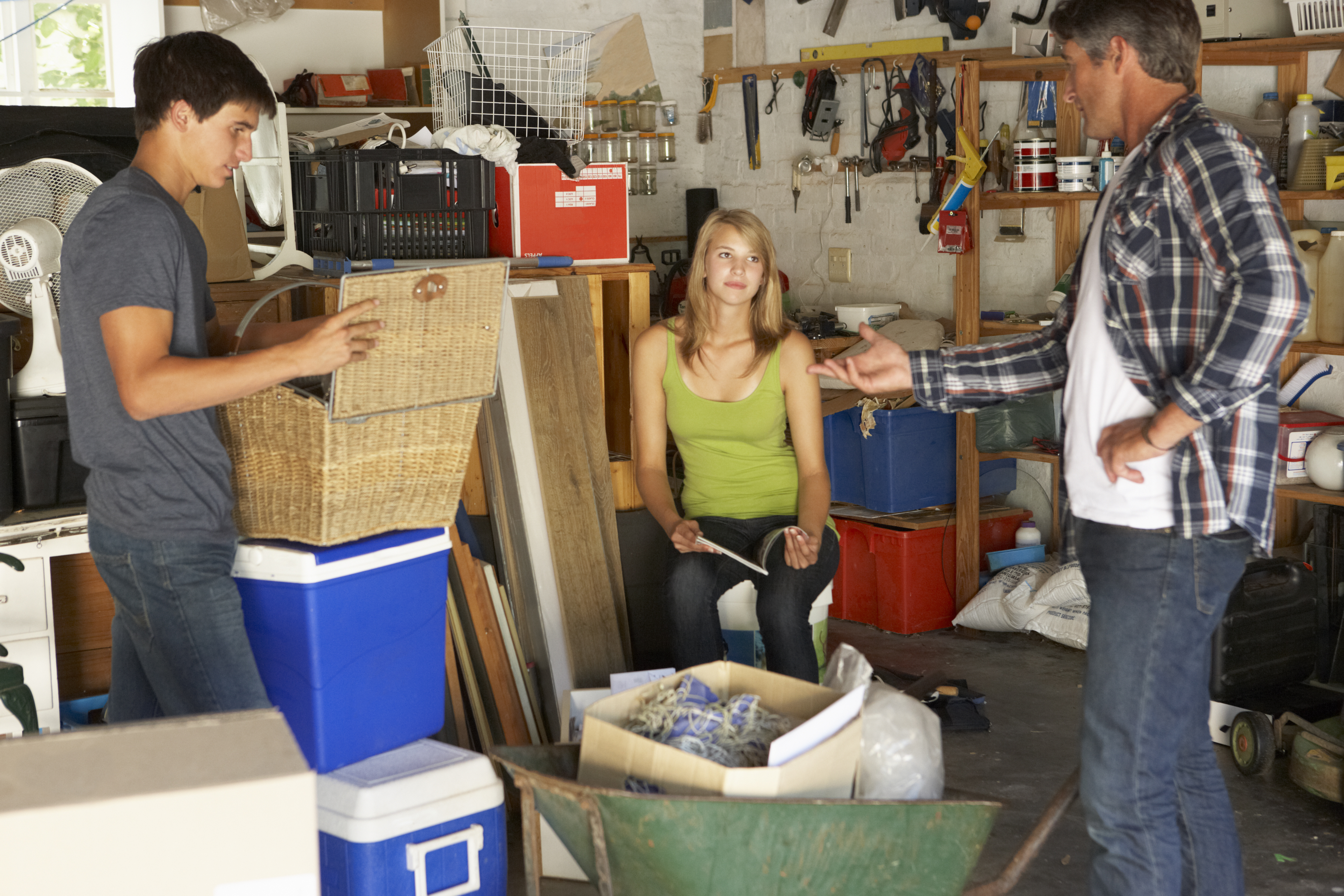 Father Organising Two Teenagers Clearing Garage For Yard Sale